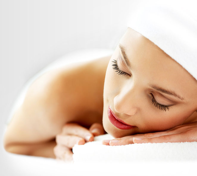Lady lying on table with white towel on her head